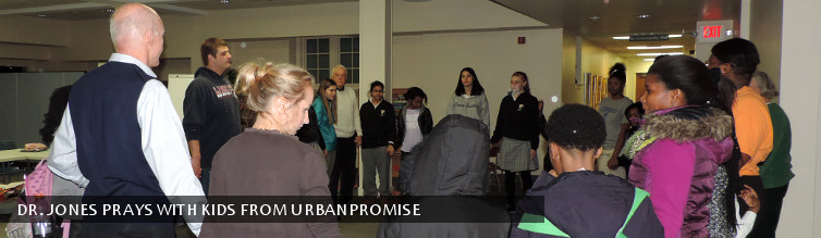 Dr. Jones prays with kids from UrbanPromise